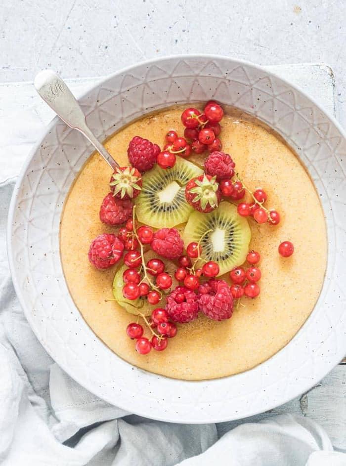instant pot breakfast porridge with kiwi and rasbperries in a bowl