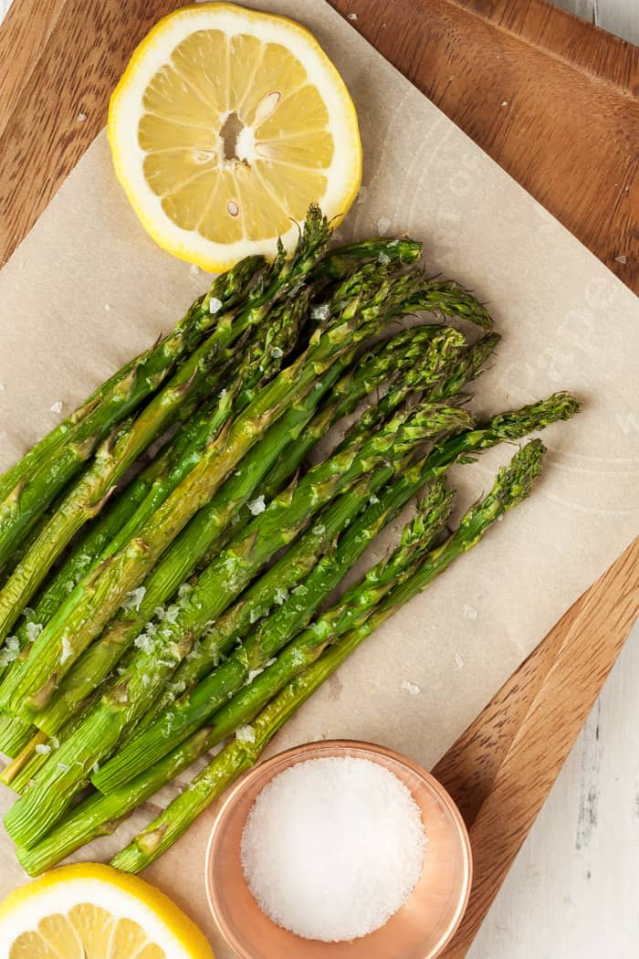 a plate of air fryer asparagus with lemon and salt