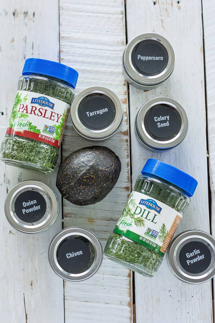 an avocado with jars of herbs and spices for making dairy-free ranch dressing