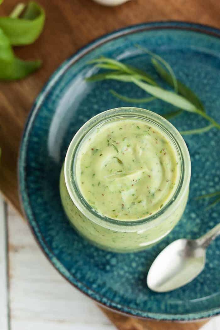 a jar of avocado ranch on a blue plate with herbs and a spoon