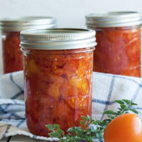 three jars of canned stewed tomatoes with herbs