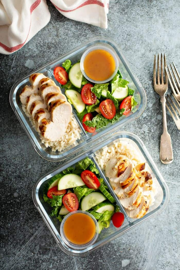 two glass containers with meal prepped food and forks