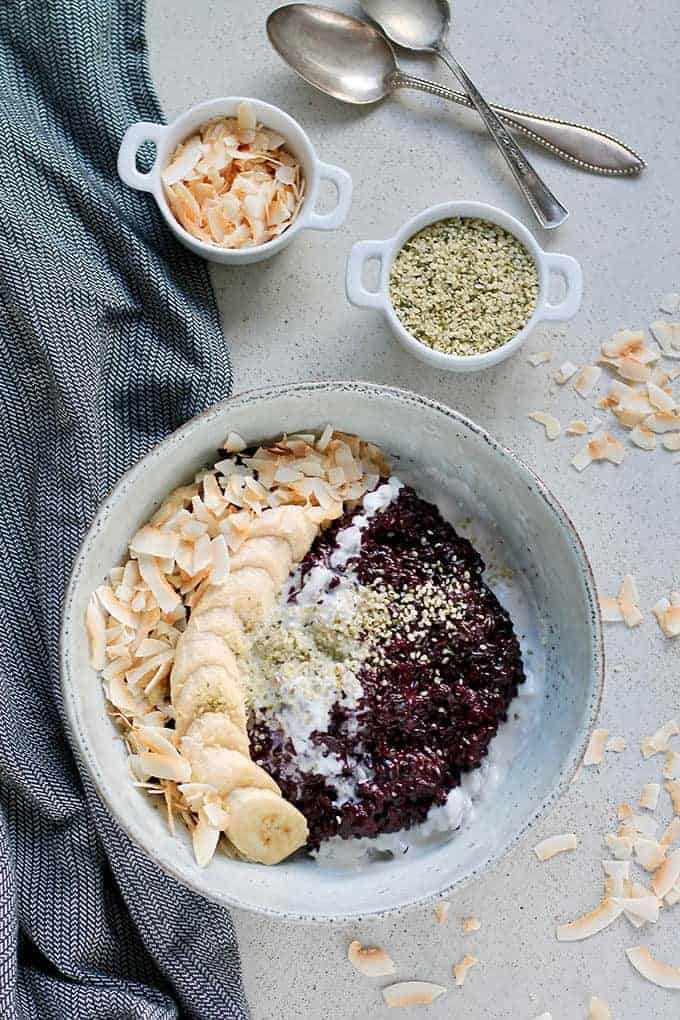 a bowl of black rice indonesian pudding with banans and toasted coconut