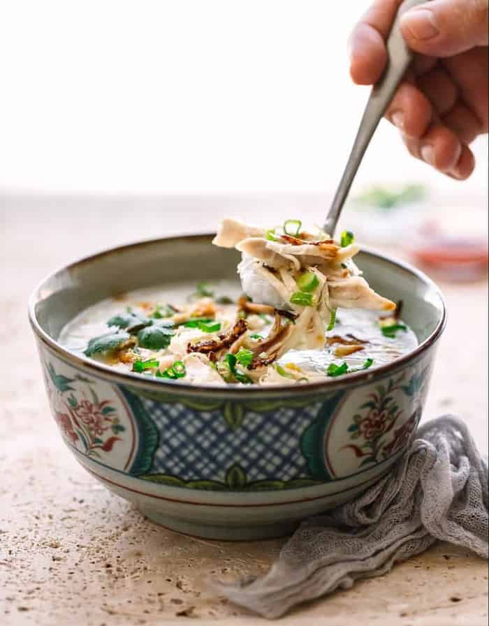 a spoon lifting up a bite of instant pot congee