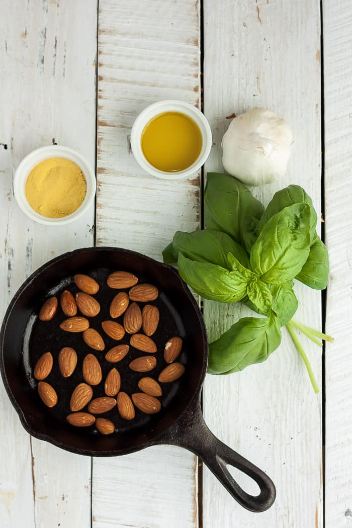 a cast iron skillet with almonds, and other ingredients for making pesto on a white board