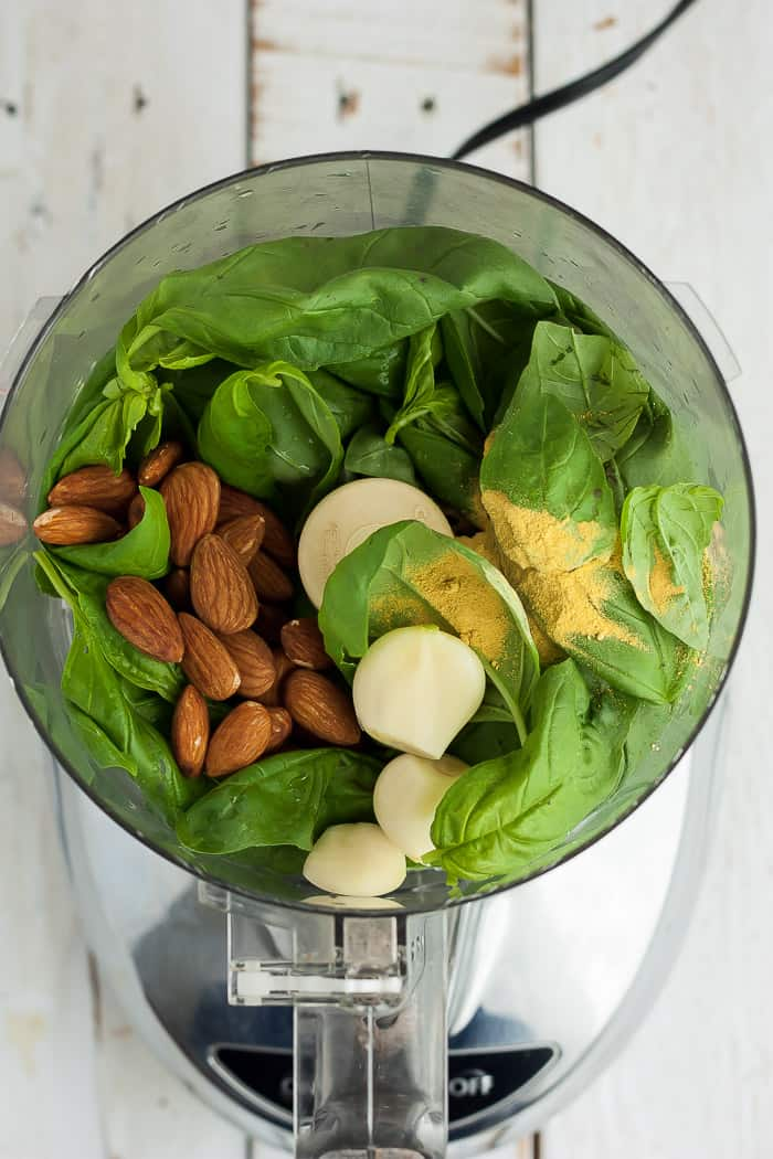 a food processor with basil, nuts, and garlic