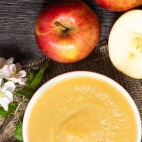 a bowl of applesauce with apples on a wooden board