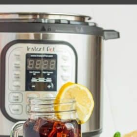 A glass of iced tea with ice and lemon in front of an Instant Pot