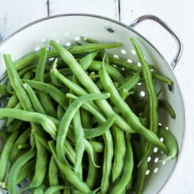a strainer of green beans on a white board
