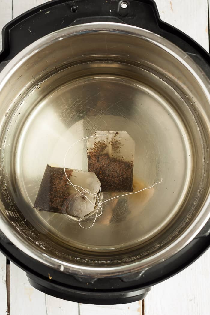 an instant pot with water and tea bags