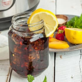 a jar of iced tea with lemon and a plate of garnishes