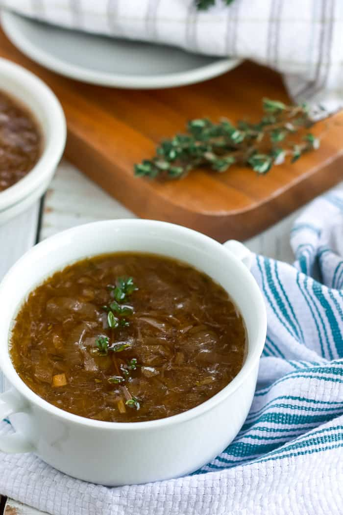 two bowls of instant pot french onion soup with herbs