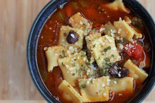 a bowl of vegetable soup with cheese ravioli