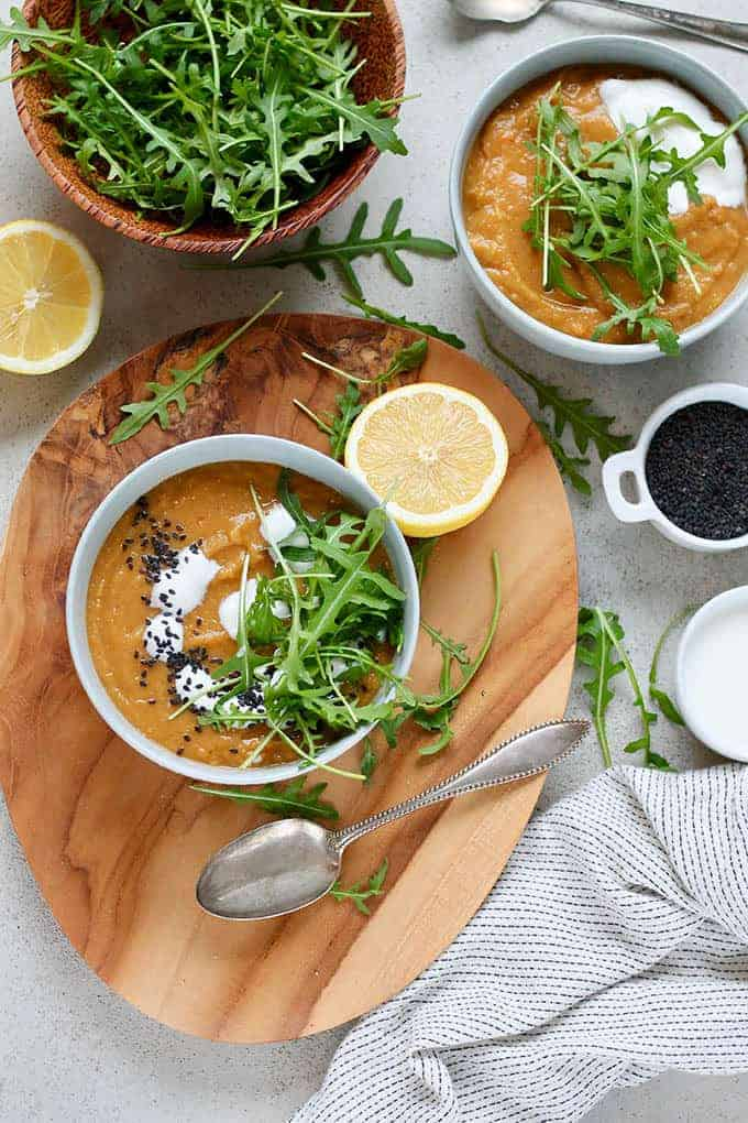 bowls of vegan carrot ginger soup on a cutting board with herbs and lemons