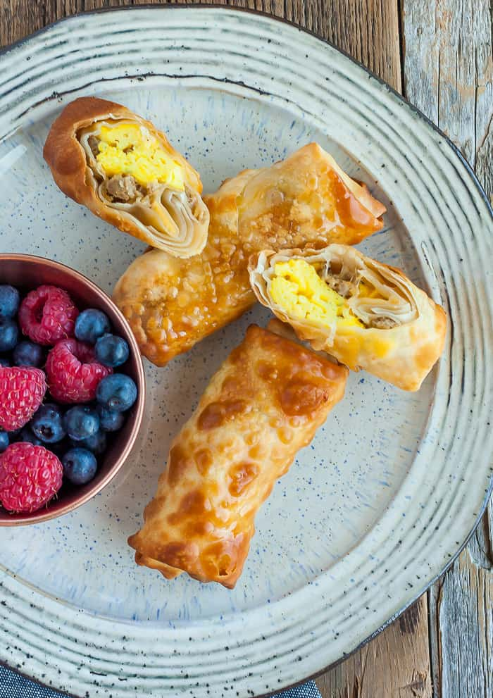 4 bacon and egg rolls and a dish of berries on a grey plate
