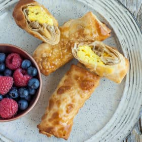bacon and egg rolls on a grey plate with berries