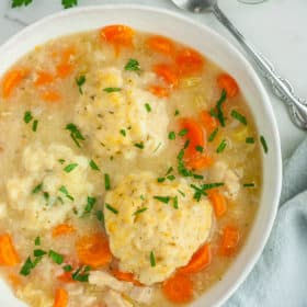 a bowl of instant pot chicken and dumplings with chopped parsley on top and a spoon