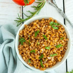 A white bowl with farro topped with chopped parsley