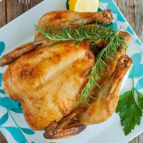 A whole chicken with rosemary and lemons on a blue and white plate