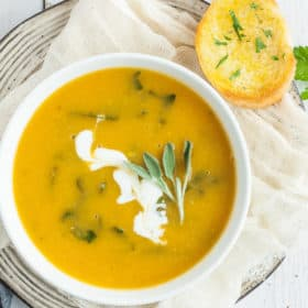 a bowl of vegan butternut squash soup with herbs and bread