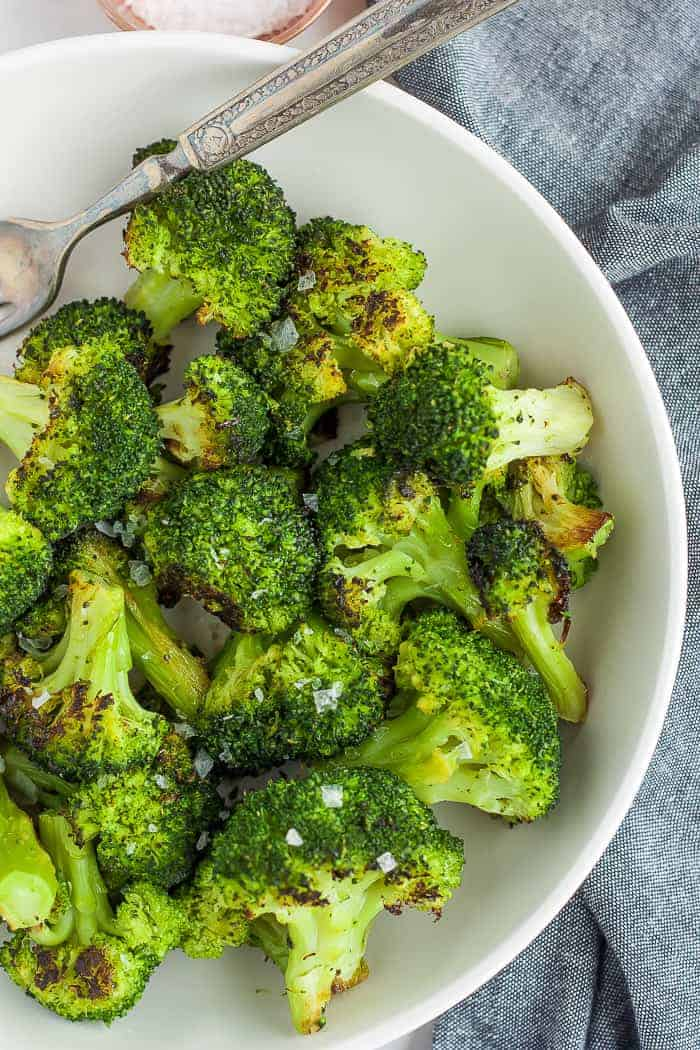 a white bowl full of roasted frozen broccoli
