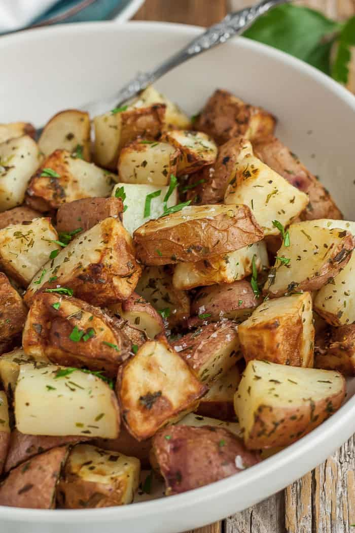 a white bowl of air fryer potatoes with parsley and a fork