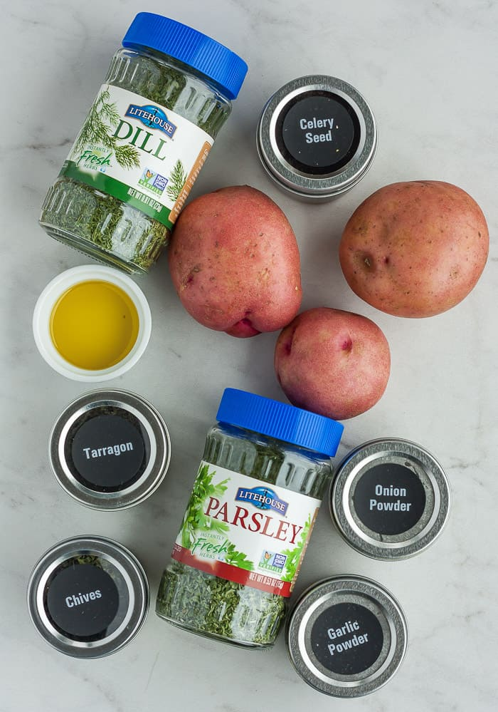 three red potatoes with parsley, a bowl of olive oil, and other herbs on a grey board