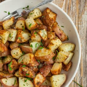 A bowl of crispy fried potatoes topped with parsley