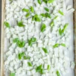a baking sheet with chopped frozen onions on a piece of parchment