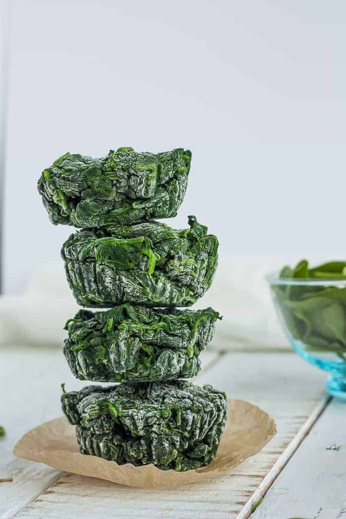 four cubes of frozen spinach stacked on top of a muffin liner