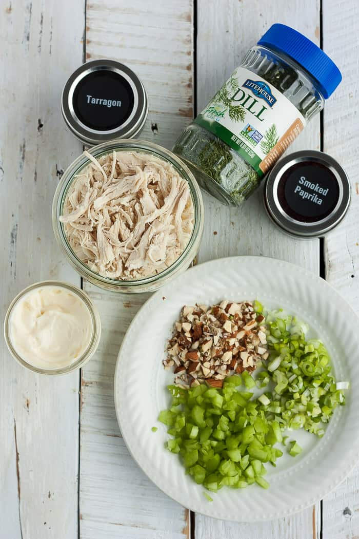 a bowl of chicken, a plate of celery and onions and other ingredients for making healthy chicken salad