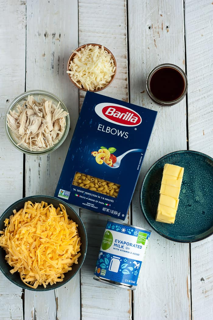 a box of noodles, butter, a can of evaporated milk, shredded cheese on a white board