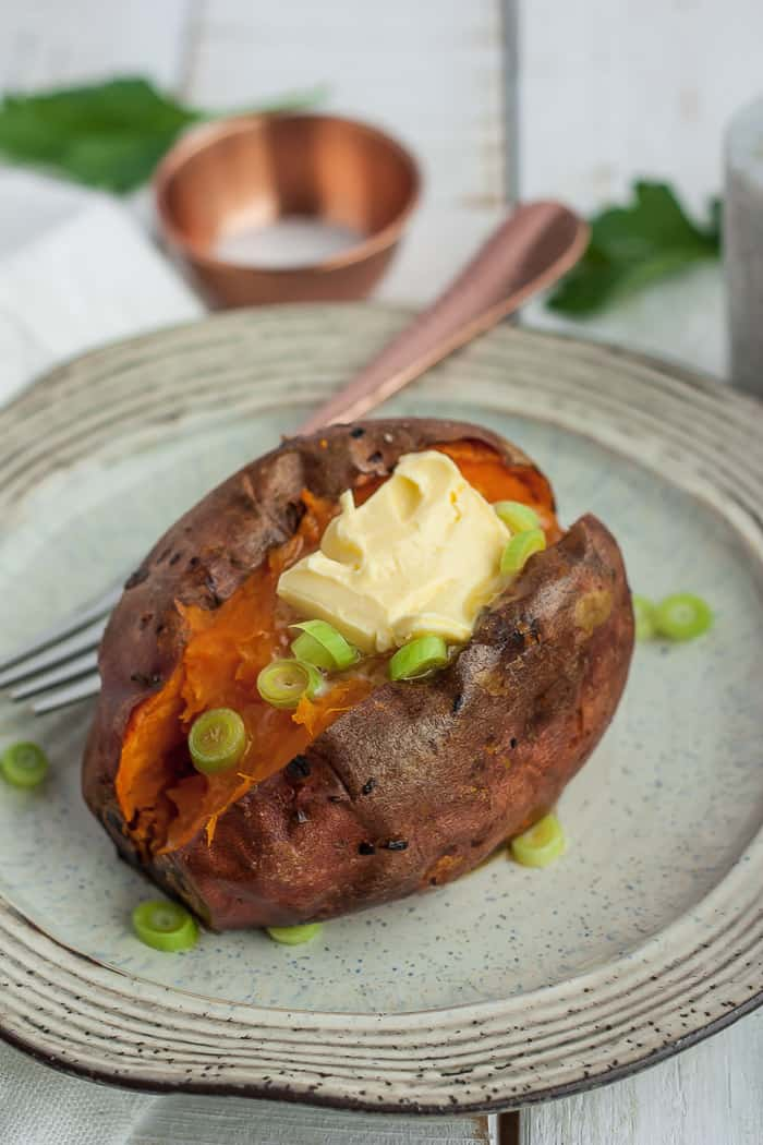 roasted sweet potato topped with butter on a plate
