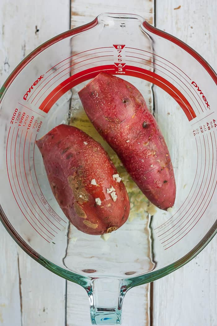 2 sweet potatoe in a glass bowl with olive oil and garlic