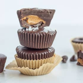 3 dark chocolate almond butter cups stacked on top of each other. Top one is cut in half