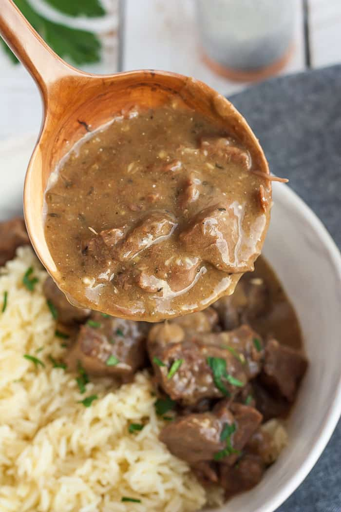 a ladle of sirloin tips and gravy over a bowl with rice and steak