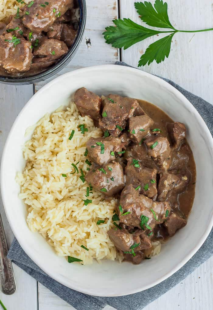 a white bowl with rice and instant pot beef tips and gravy garnished with parsley