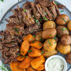 a grey plate with shredded whole30 pot roast, cut carrots, potatoes, and a bowl of horseradish,