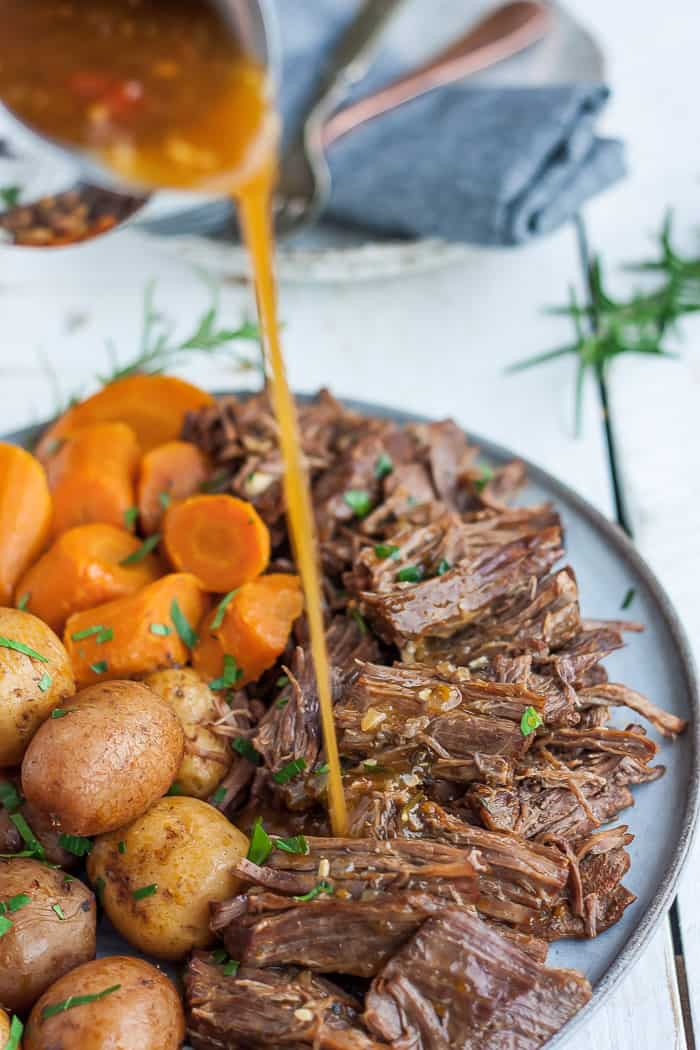a palte of shredded pot roast with a pitcher of gravy being poured onto it