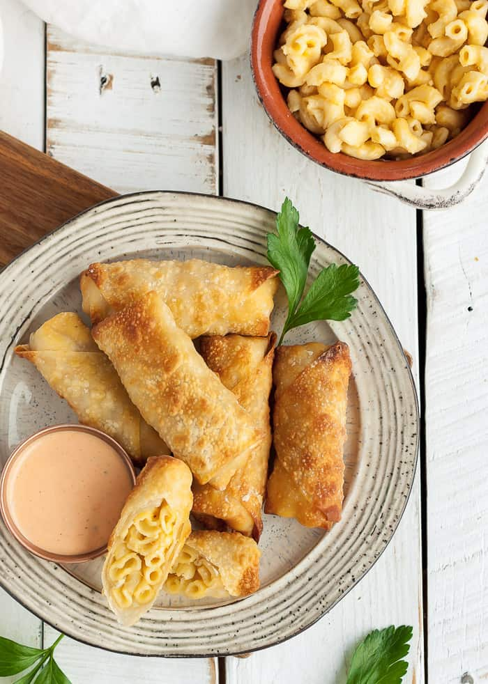 a beige plate with egg rolls and a bowl of mac and cheese on a white board