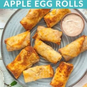 Apple Pie Egg Rolls on a grey plate with a small bowl of greek yogurt dipping sauce