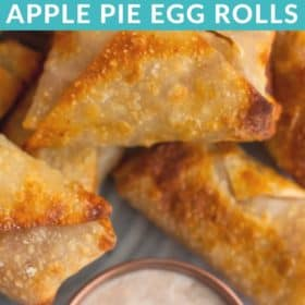 A stack of apple pie egg rolls on a grey plate with yogurt dipping sauce