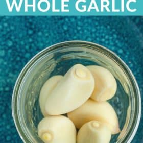 Garlic cloves in a canning jar on a blue plate