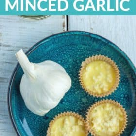 Minced garlic frozen in muffin liners on a blue plate