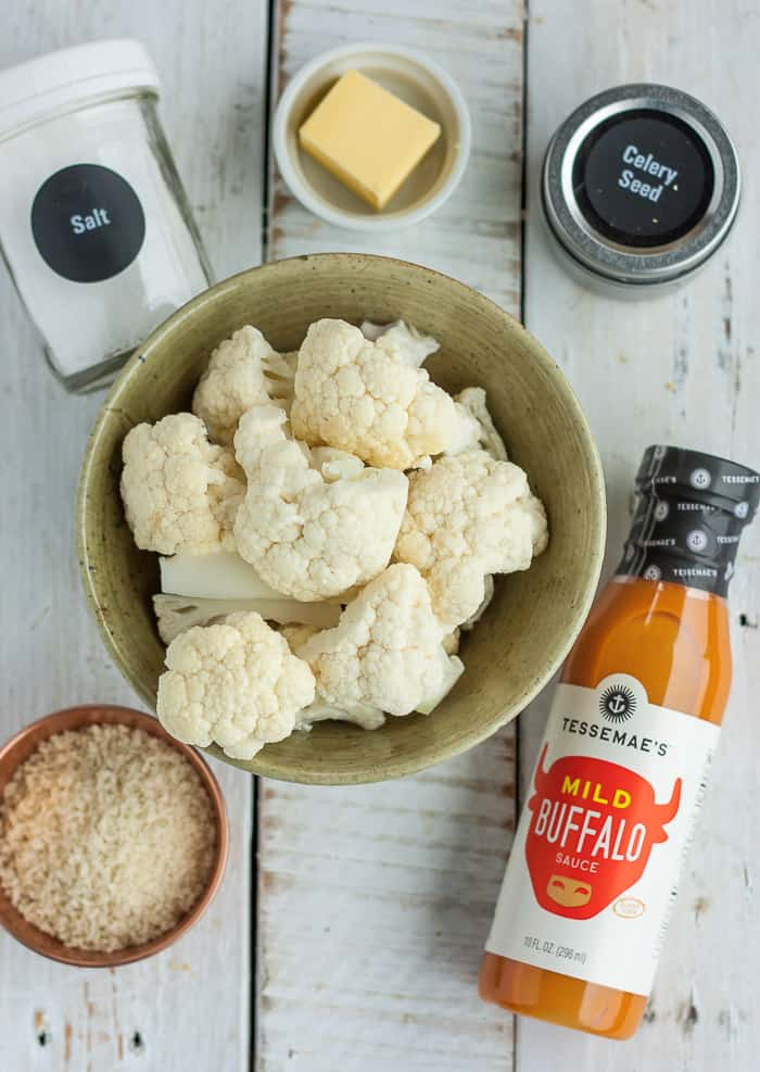 A bowl of cauliflower, buffalo sauce, and other ingredients for making air fryer buffalo cauliflower