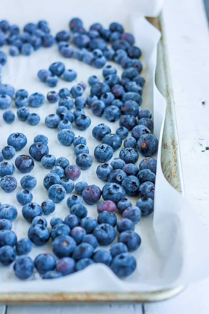 a tray with frozen blueberries on parchment