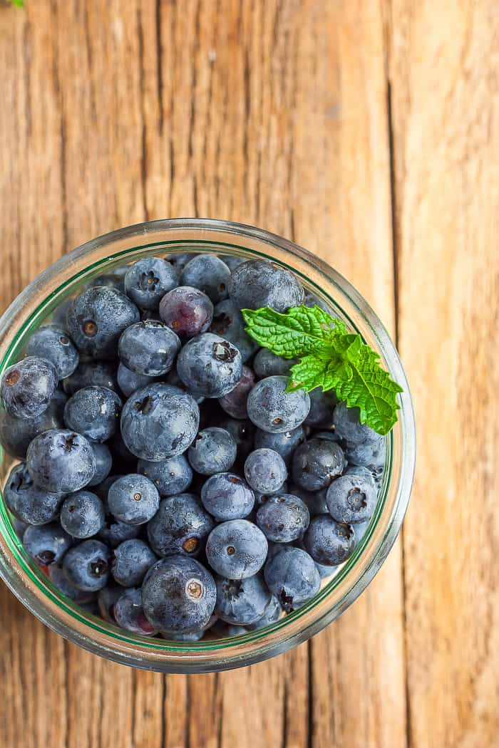 A glass bowl full of blueberries and a sprig of mint on a wooden board