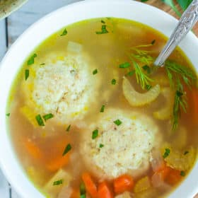 A white bowl with matzo ball soup and fresh dill