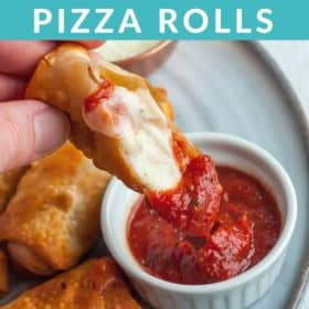 A hand dipping a pizza roll into a bowl of sauce