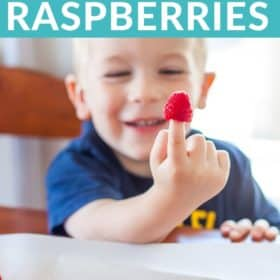a boy holding a frozen raspberry on his finger